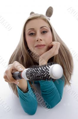 laying woman holding roller comb