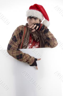 boy wearing christmas hat pointing placard