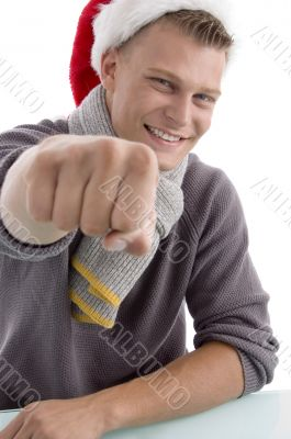 smiling young man with christmas hat showing punch
