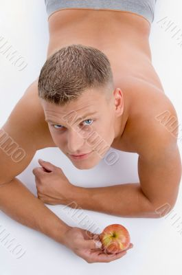 high angle view of muscular man with apple