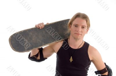 handsome guy holding skateboard on his shoulder
