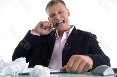 frustrated man biting on pen with teeth