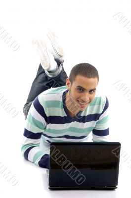 young male lying on the floor and busy with laptop