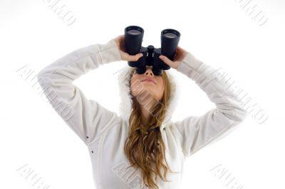 female watching upward through binocular