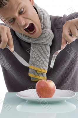 young man going to eat apple with fork and knife