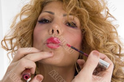 beautician doing lip make up of woman