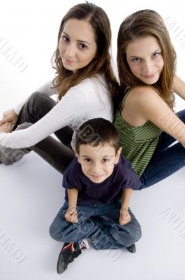 young kid sitting with teenagers