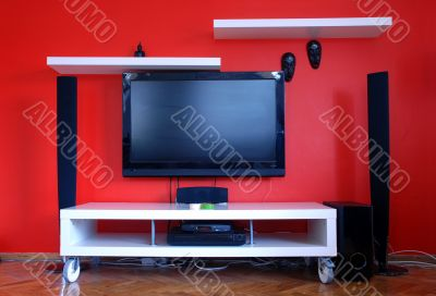 big lcd televison on red wall, vivid bright colors