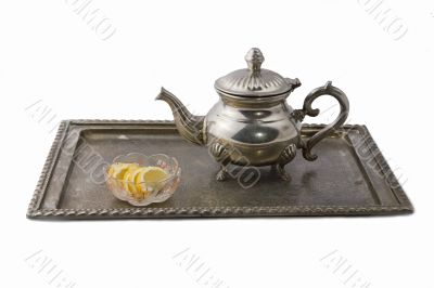 Teapot on a tray served with lemon slices