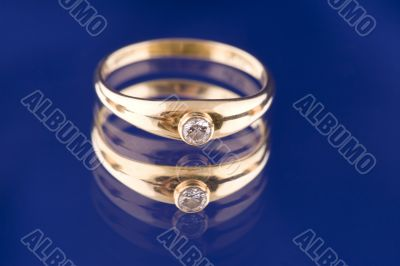 Golden ring with stone on blue