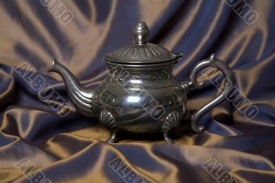 Teapot on a grey drapery background