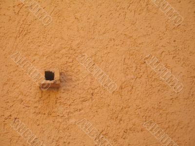 small drain in a orange wall