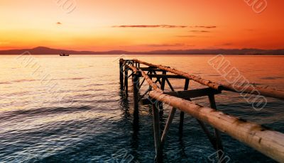Primitive wooden pier at sunset