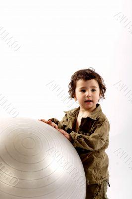Little boy with big silver ball