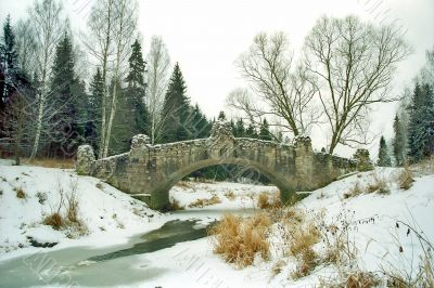 Ancient bridge over iced river