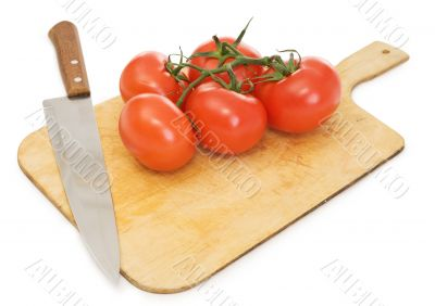 Red tomatoes and kitchen knife on a chopping board