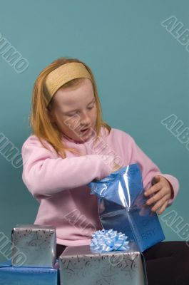 little red girl is opening her christmas presents