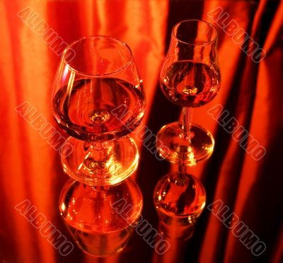 Two glasses with brandy on mirror