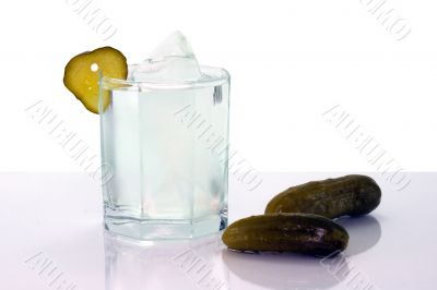 Vodka with ice in glass and salt cucumbers