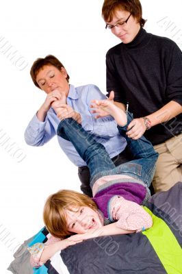 Mother and son are tickling the boy