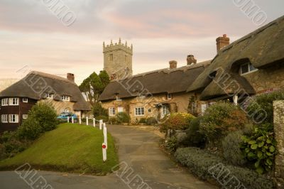 Idyllic hamlet of thatched cottages at sunset