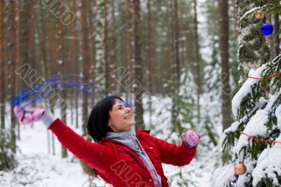 Joyful girl decorates a firtree