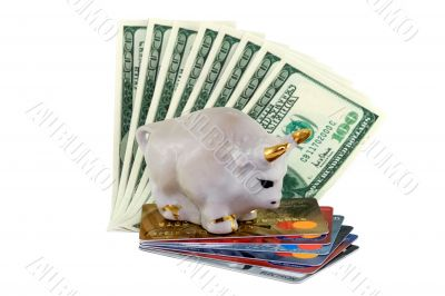 Figure of a white bull with gold horns standing on a pile of credit cards and dollars