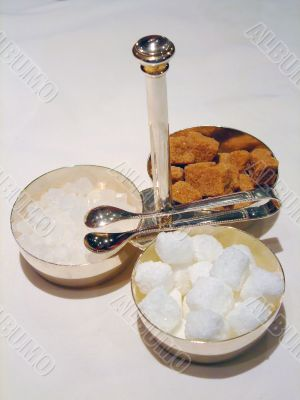 Bowls with cane sugar, white sugar and candy sugar