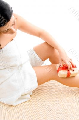 woman scrubbing her legs on white background