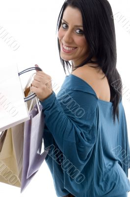 side view of smiling model carrying carry bags