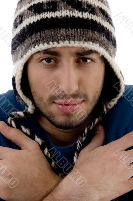 man wearing winter cap shivering from cold