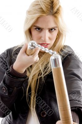 front view of aggressive female holding nunchaku