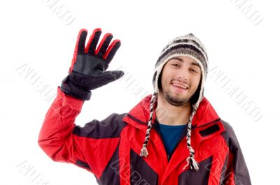 man wearing winter cap and jacket waving hello