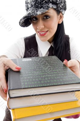 student in cap holding stack of books