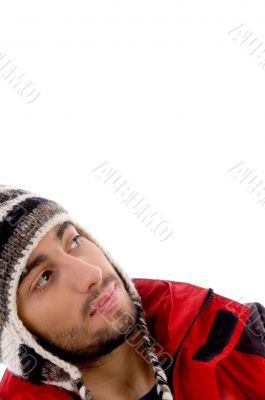 smart young guy in winter cap looking sideways