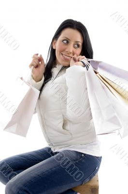 side pose of smiling woman holding shopping bags