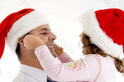 daughter stretching father`s cheeks