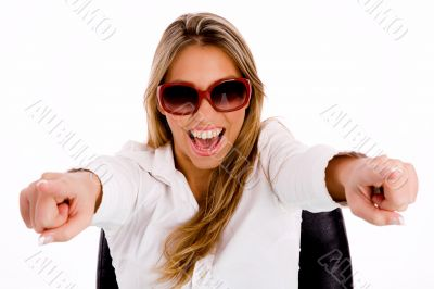 female with sunglasses pointing with both hand