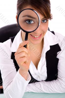 smiling young woman holding magnifier