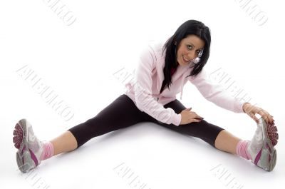 side view of smiling woman stretching her legs