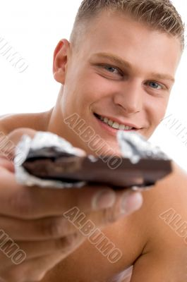 muscular man offering chocolate