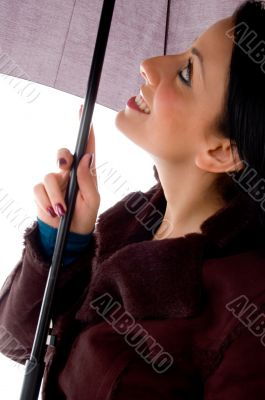 side view of smiling woman looking umbrella