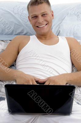 smiling guy posing with laptop