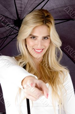 happy female holding an umbrella pointing at camer