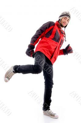 handsome guy wearing woolen cap and jacket kicking