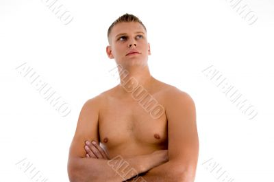 muscular man with crossed arms looking upward