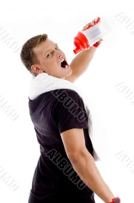 muscular man drinking from water bottle