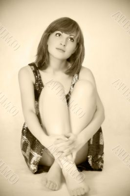 Young beautiful woman sitting on floor, sepia toned