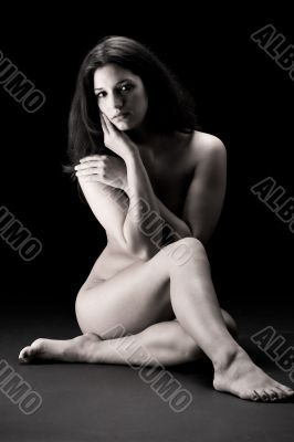 naked brunette in a low key setting sitting