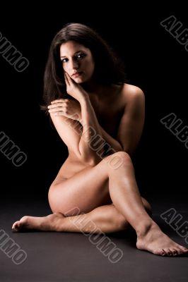 naked brunette in a low key setting flirting